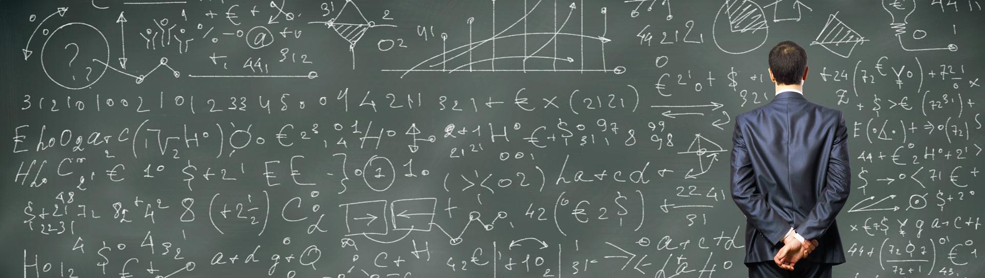 Empresario ante una pizarra llena de fórmulas y gráficas